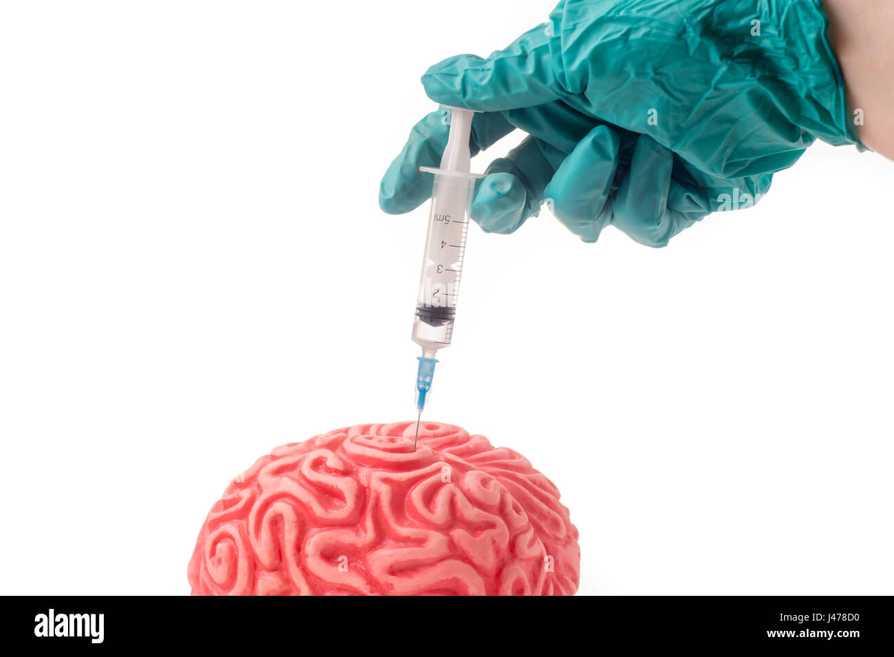 Brain injected with unknown drug. The injection is given by hand with green protective glove and is isolated on - Stock Image