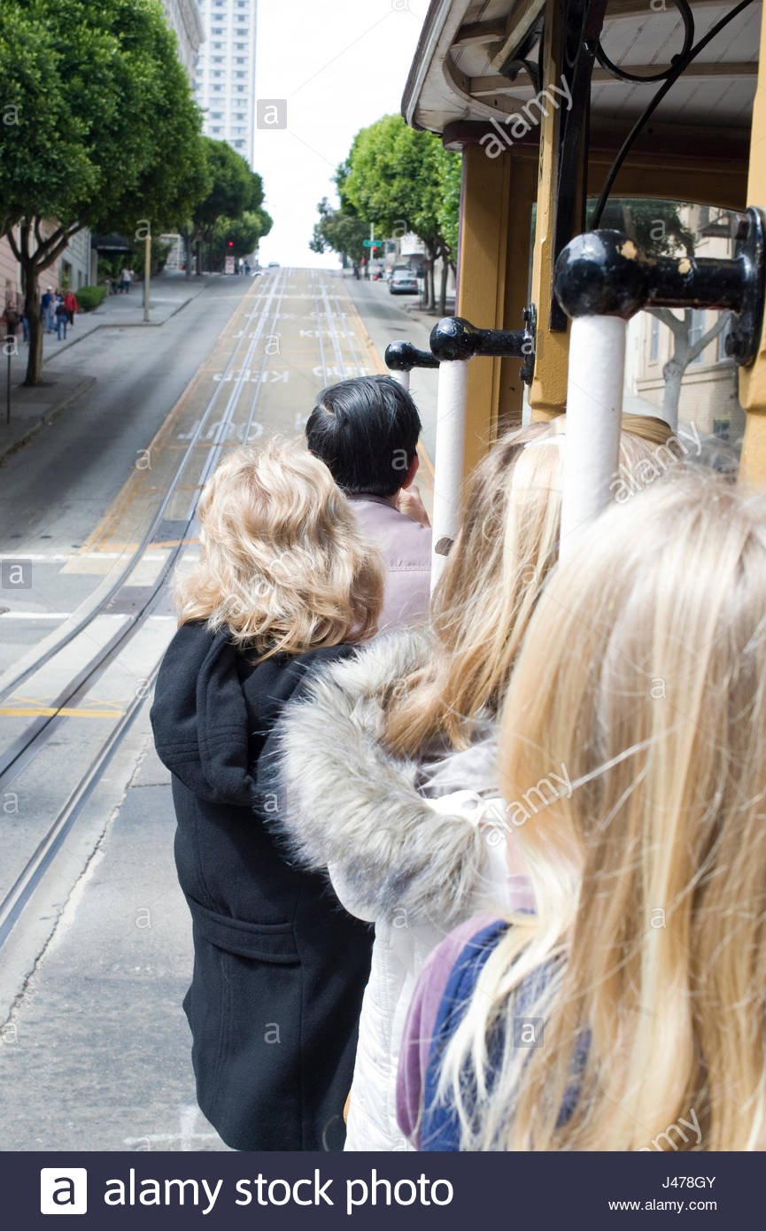 People standing on sideboards and holding onto grab bars of cable car as it ascends Powell Street, San Francisco, Stock Photo