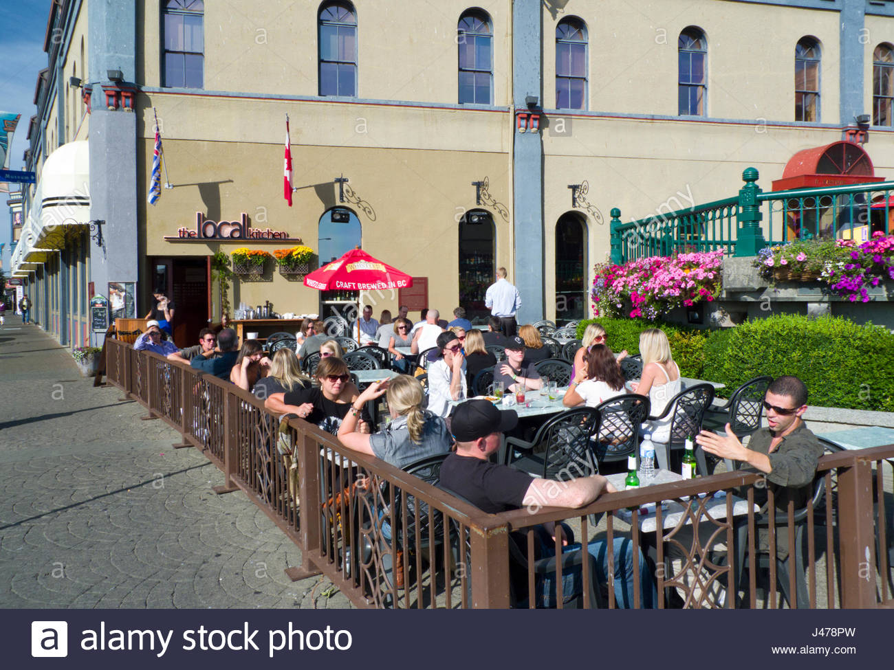 People Sitting At Tables Outside Enjoying The Sunny Weather