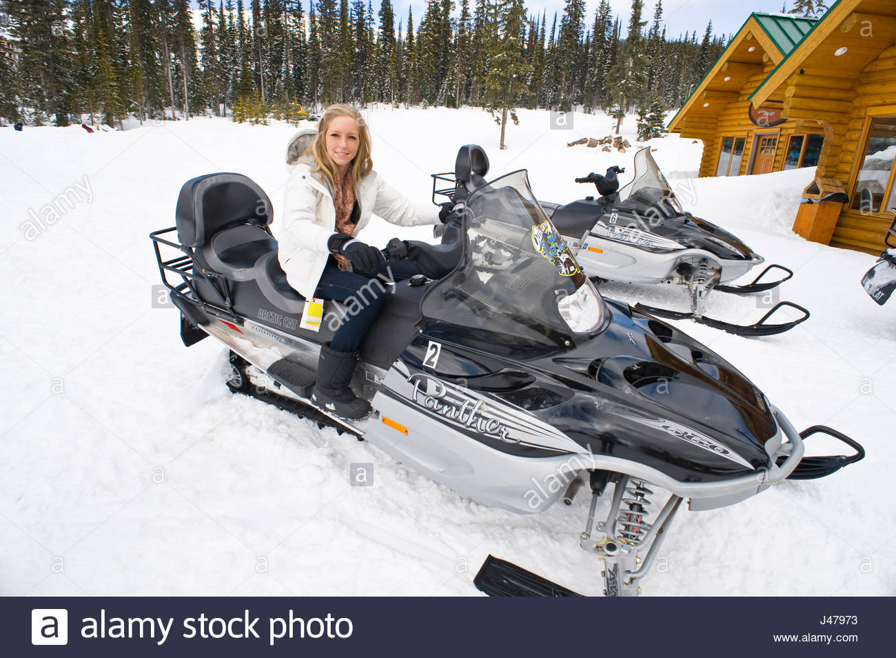 Teenage girl sitting on a Snowmobile parked in front of log cabins in Adventure Park, Big White, British Columbia, - Stock Image