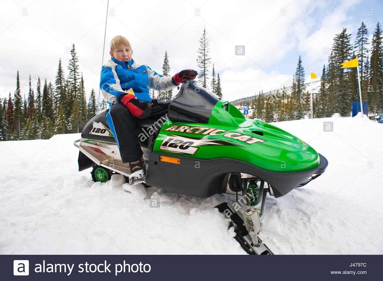 Boy sitting on a Snowmobile Adventure Park, Big White, British Columbia, Canada - Stock Image
