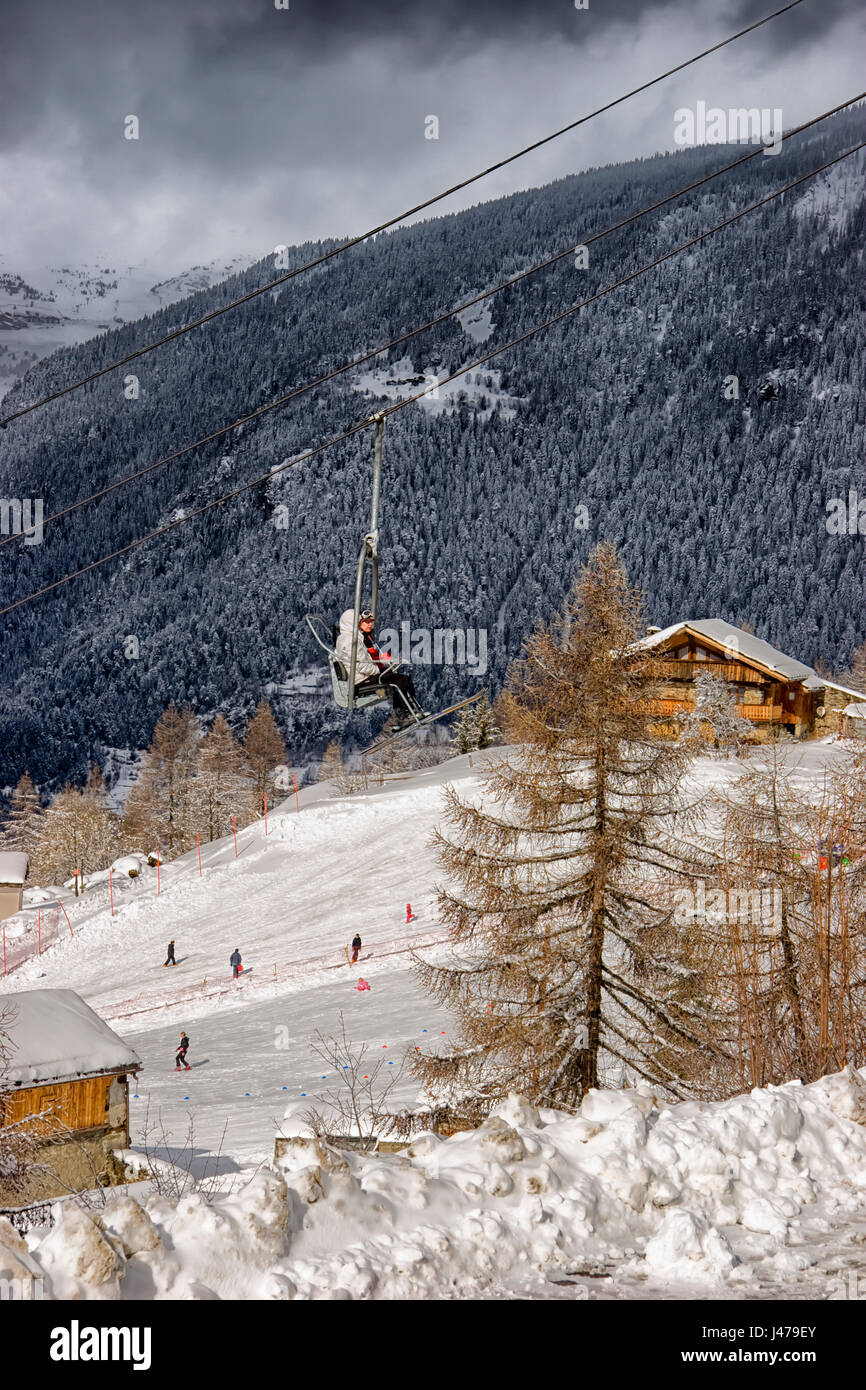 Skiers travelling on a ski lift, with skiers using the slopes below, Sainte Foy, Northern French Alps, France - Stock Image