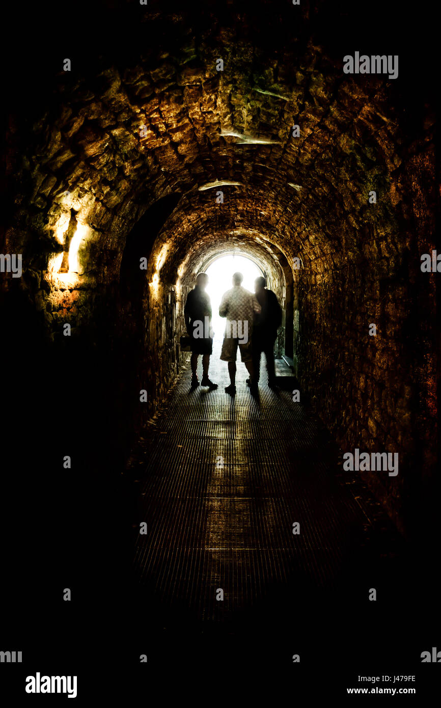 3 men talking at the end of a dark brick tunnel - Stock Image