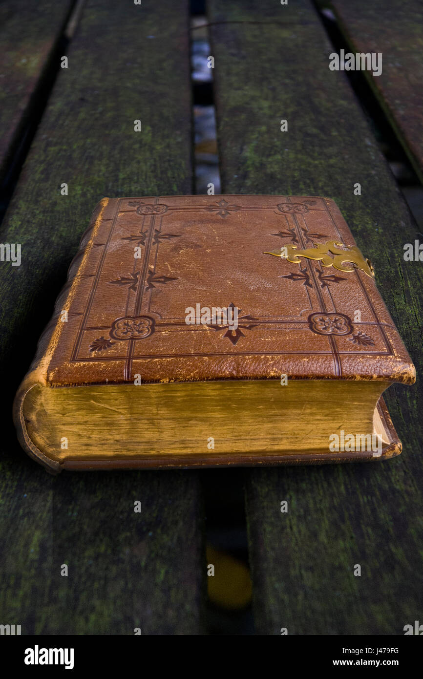 Antique tooled brown leather bound book with metal clasp on a wooden background - Stock Image
