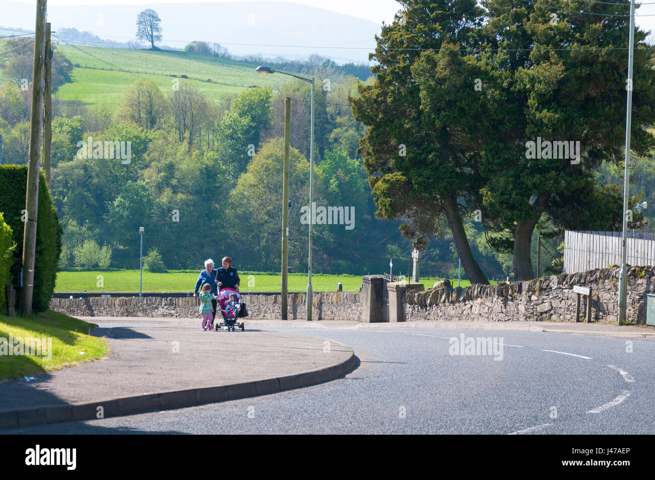 Claudy bombing, Main Street, County Londonderry, Northern Ireland. People walking with children and buggy pushchair - Stock Image