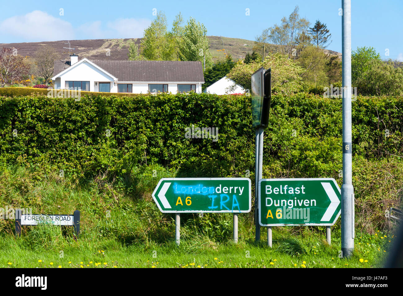 Defaced road sign near Claudy in County Londonderry, Northern Ireland UK. - Stock Image