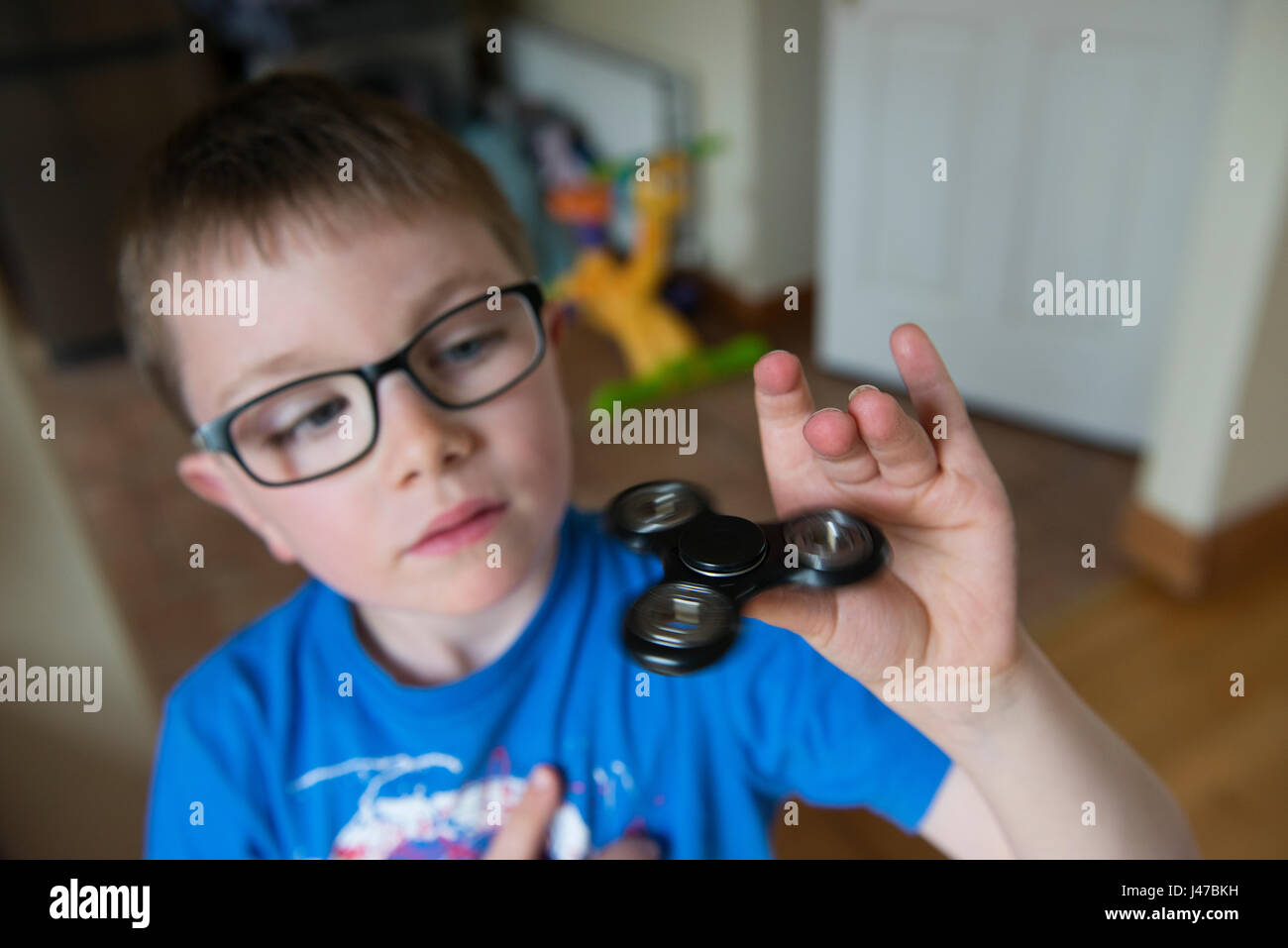 A young boy spins a black fidget spinner on his thumb - Stock Image
