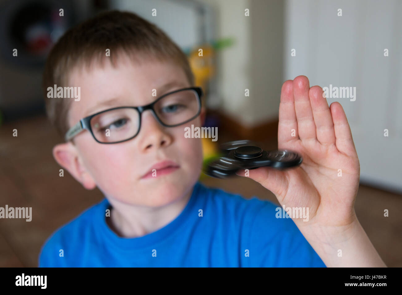 A closeup crop of a young boy spinning a black fidget spinner on his thumb - Stock Image