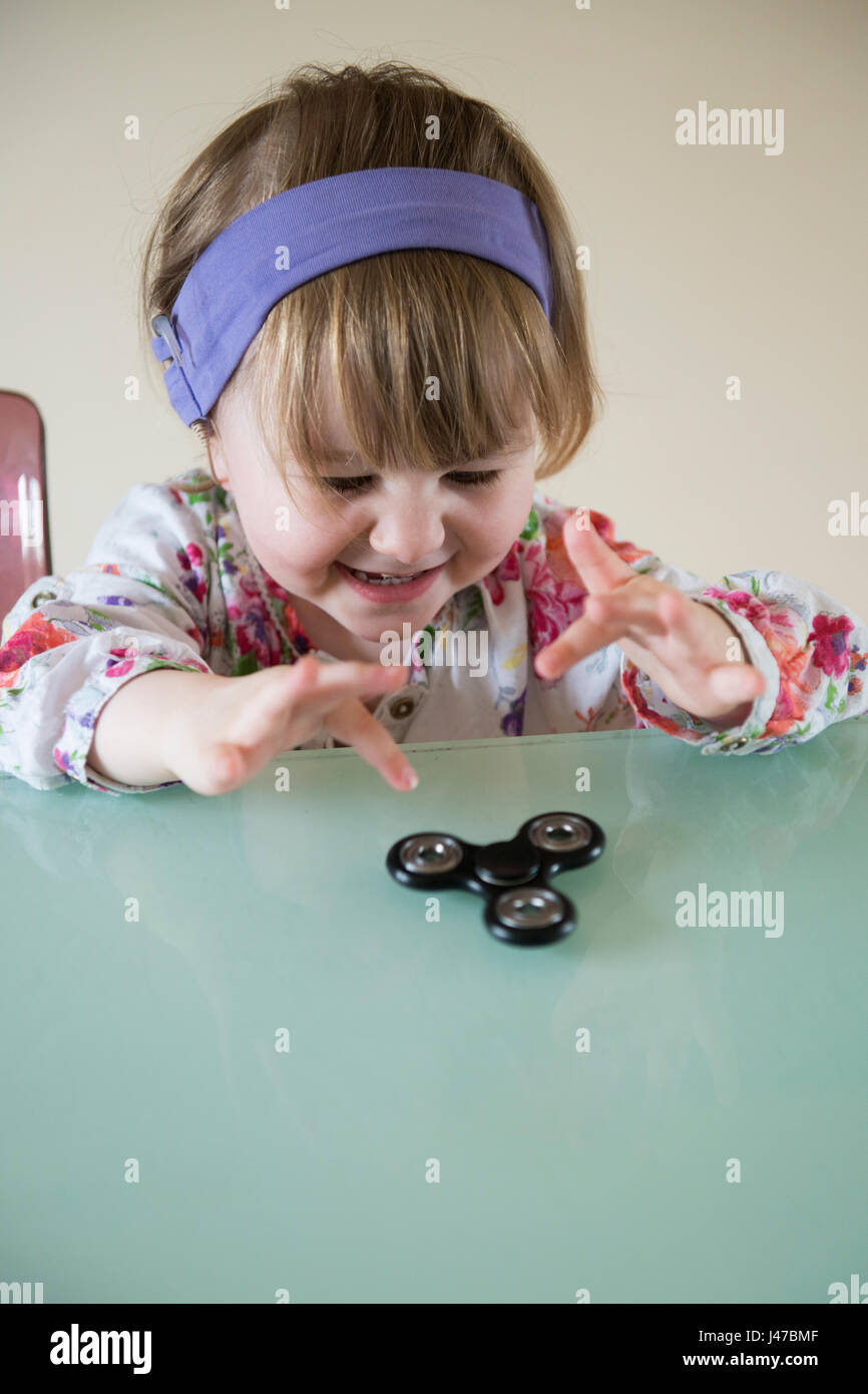 A smiling little girl plays with a black fidget spinner on a glass table - Stock Image