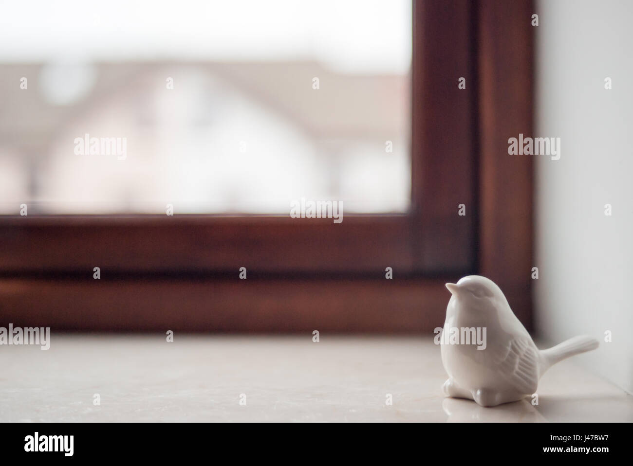 A window with a clay sparrow on a marble window sill - Stock Image