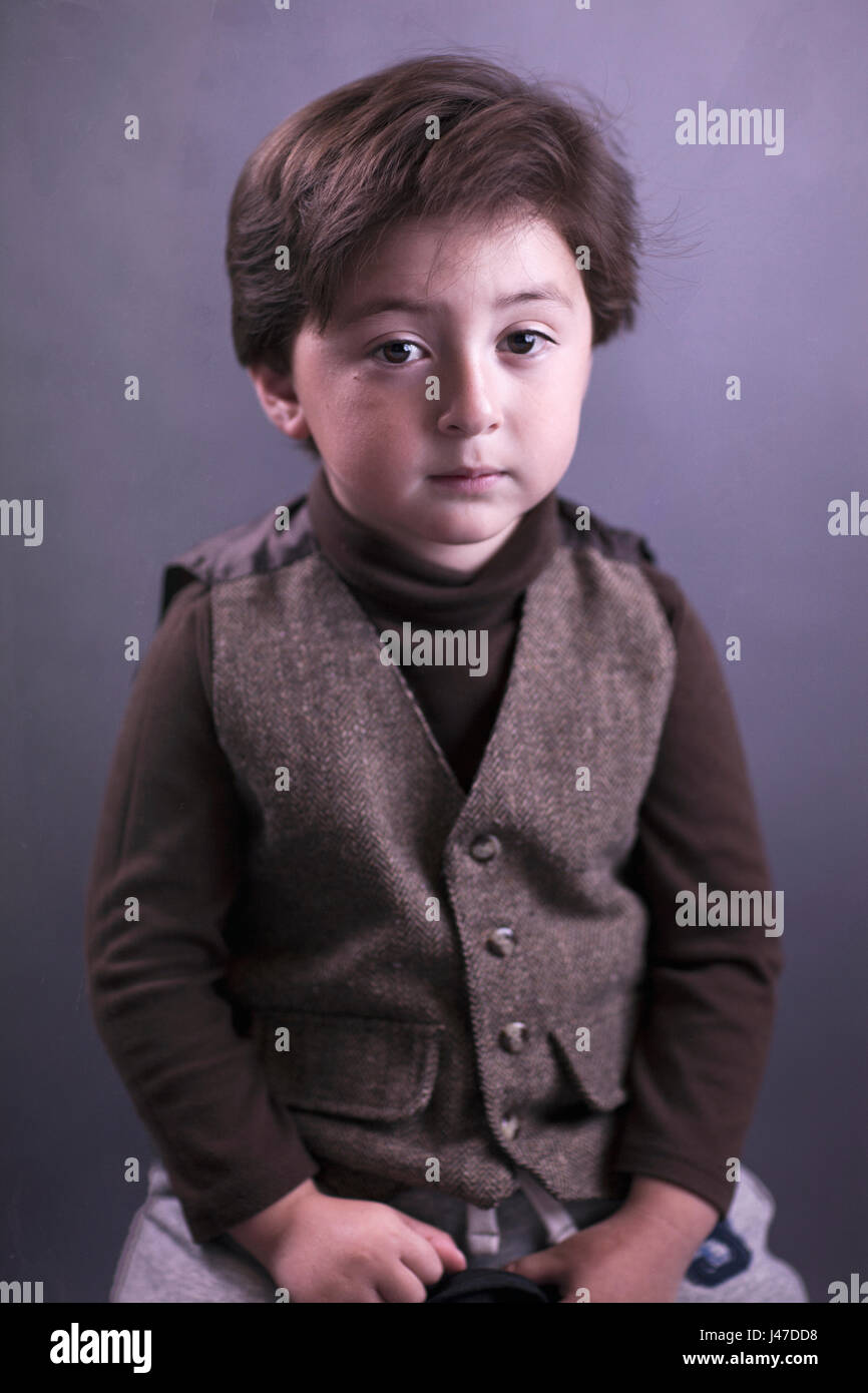 Portrait of a handsome little boy with a brown turtleneck sweater and brown tweed vest with full head of thick brown - Stock Image