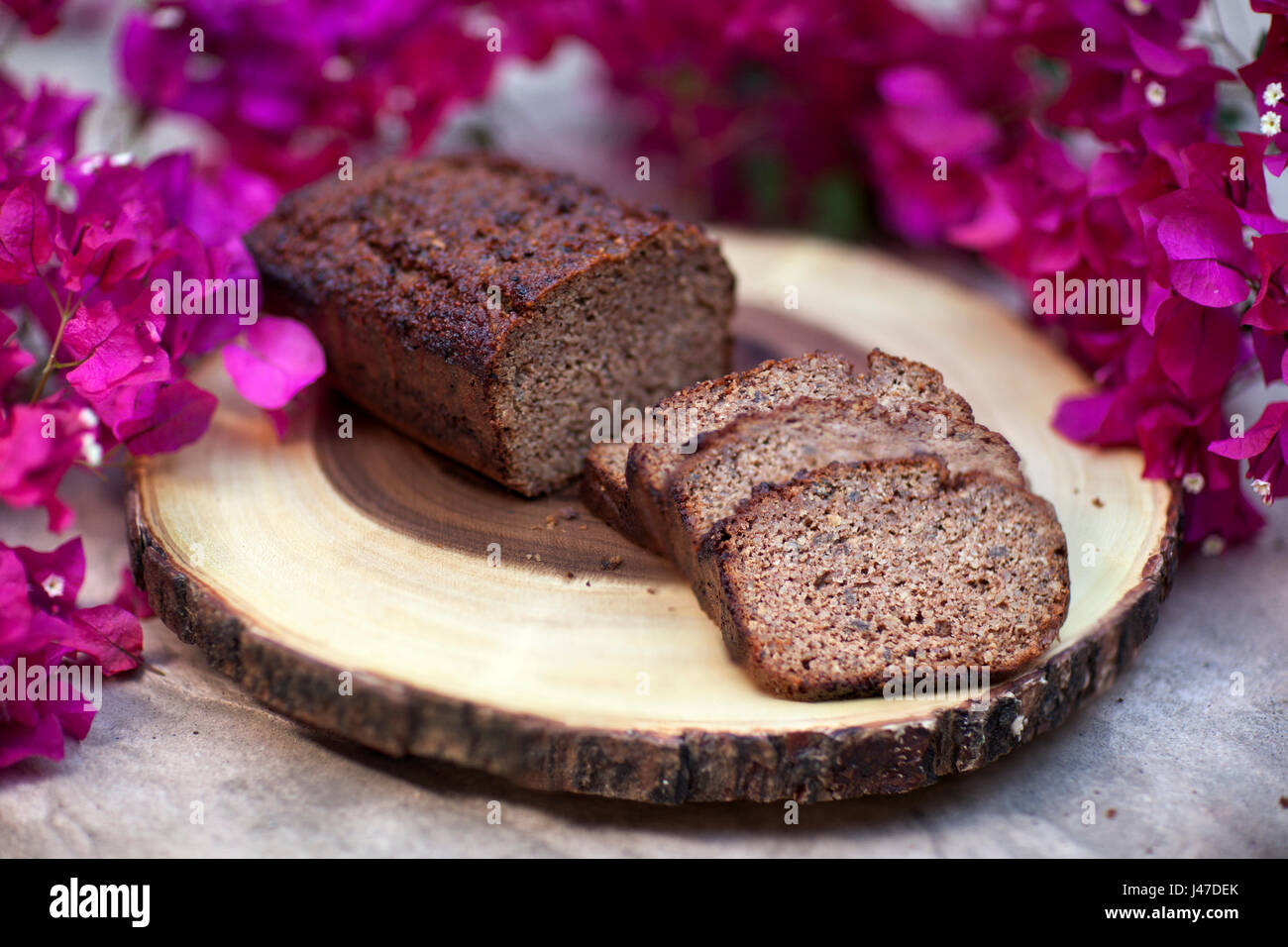 Homemade Banana Walnut bread sliced and displayed on wood-grain cutting board surrounded by pink bougainvillea flowers - Stock Image