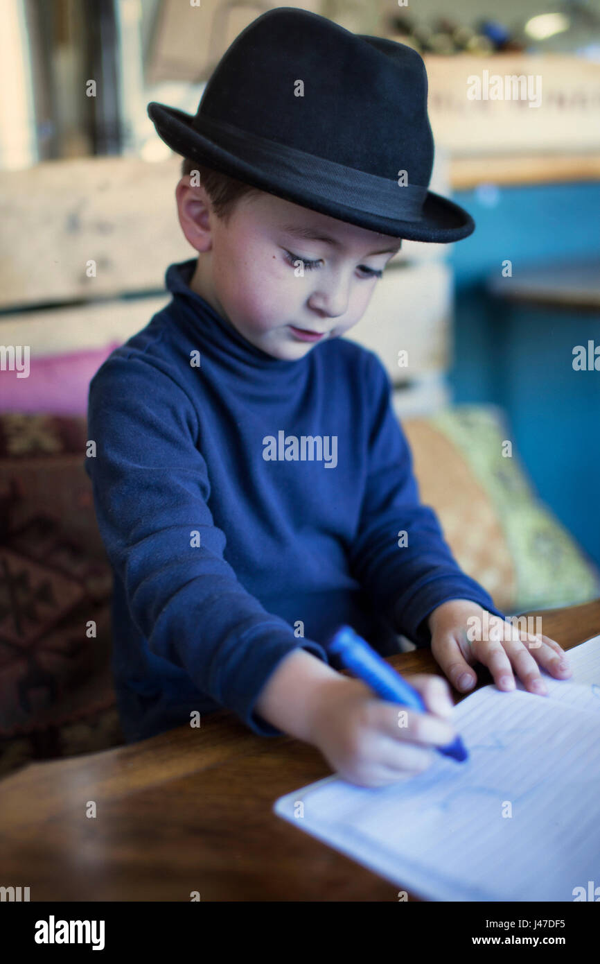 faae96426 Cute little boy with brown hair wearing a black fedora hat and a ...