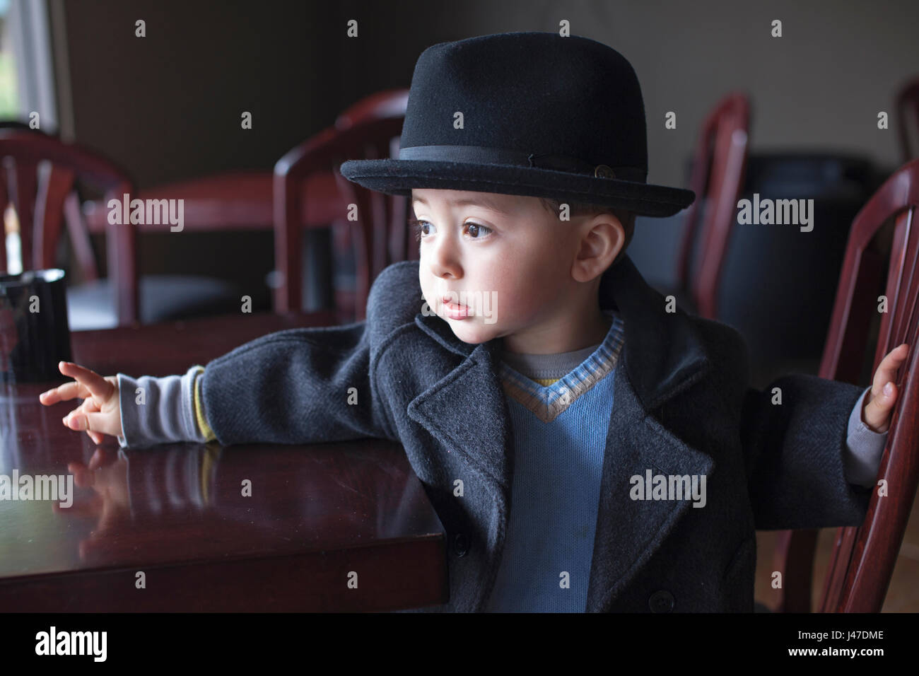 Cute mixed race Asian Caucasian little boy wearing a blue sweater and gray pea-coat with a black fedora looks out - Stock Image