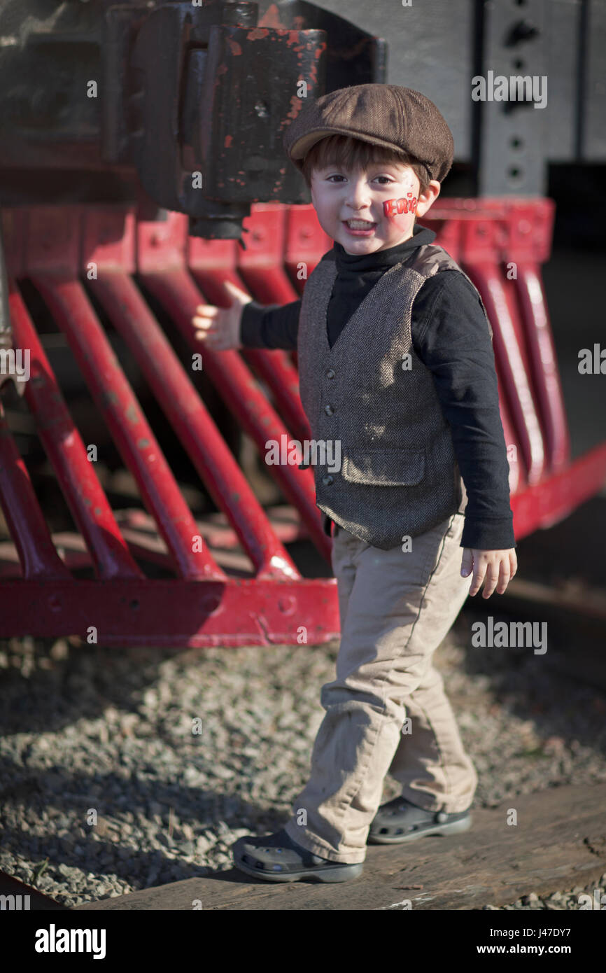 Little boy in black turtleneck shirt and brown tweed vest with brown newsboy cap walking in front of antique train - Stock Image
