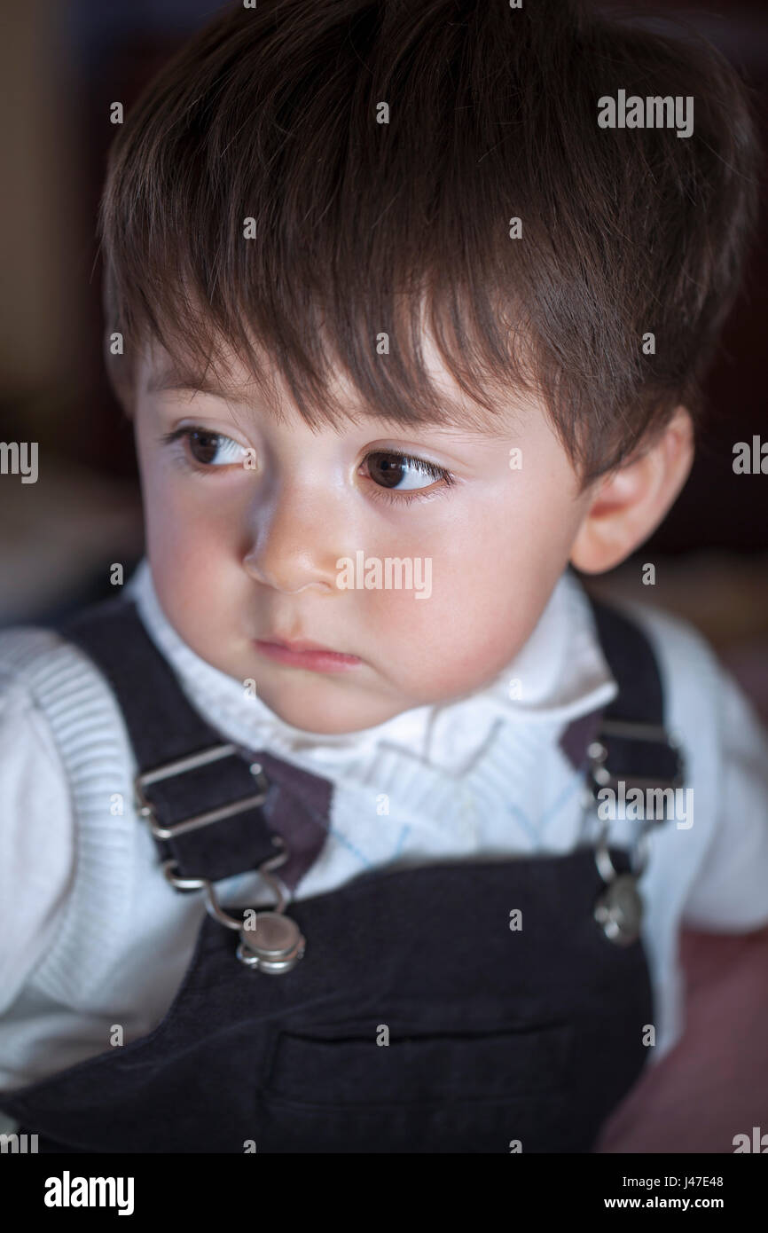 Portrait of sad serious multi-racial Asian Caucasian little boy in a white polo shirt and blue bib overalls with - Stock Image