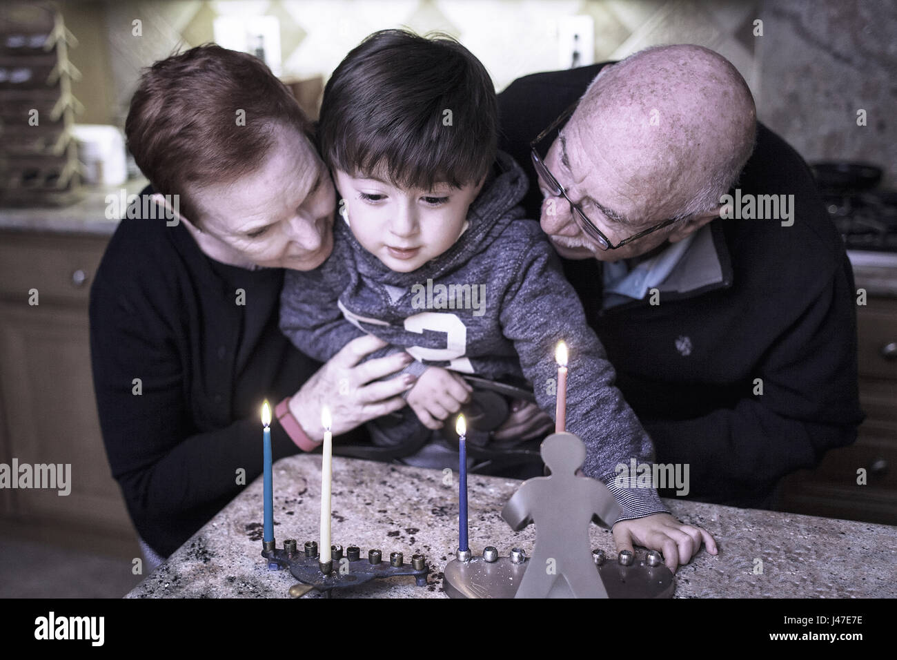 Jewish Family of grandparents and grandson lighting Hanukkah Candles in a menorah for the holdiays - Stock Image