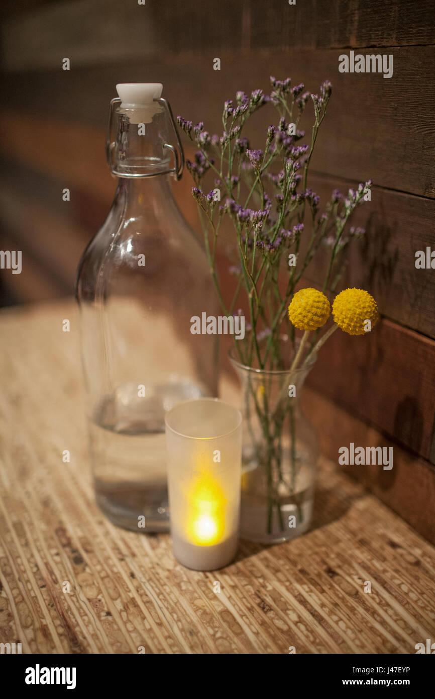 Yellow and purple dried flowers and lavender flowers in ball glass yellow and purple dried flowers and lavender flowers in ball glass jar between vintage water bottle and small candle on wood table mightylinksfo