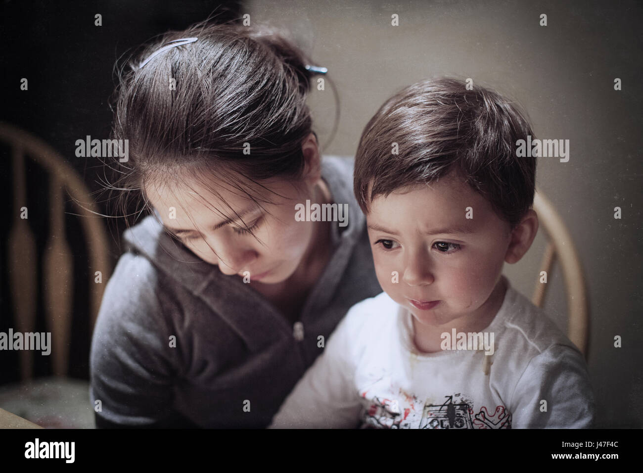 Dramatic portrait of a young Asian woman and her young son mourning the death of a father Stock Photo