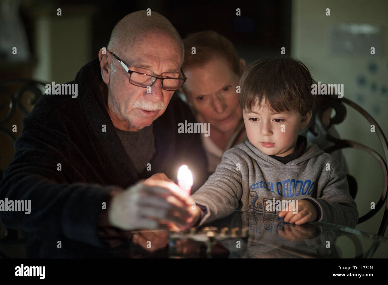 Jewish family of grandparents and their grandson lighting Hanukkah Candles in a menorah for the holdiays - Stock Image