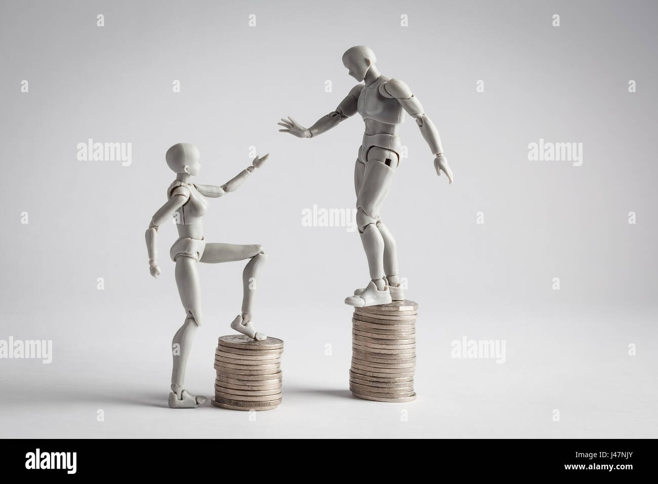 Income inequality concept shown with realistic male and female figurines and piles of coins. Female figurine extending - Stock Image