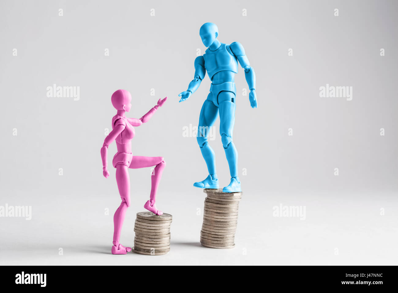 Income inequality concept shown with realistic male and female figurines and piles of coins - Stock Image
