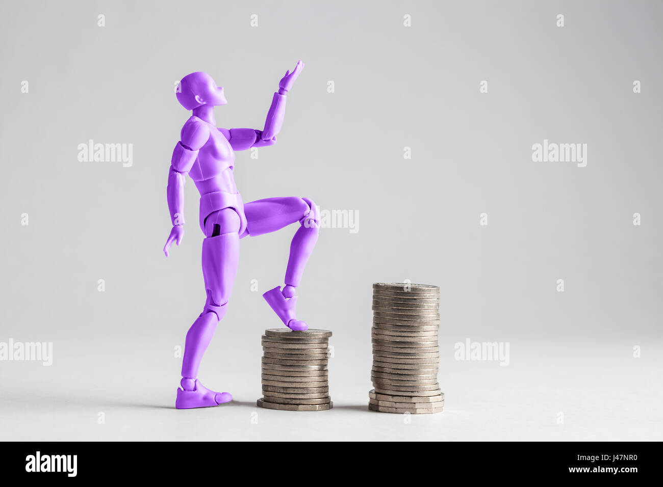 Empowered women stepping up the income ladder concept. Purple female figurine clilmbing up on piles of coins. Isolated Stock Photo