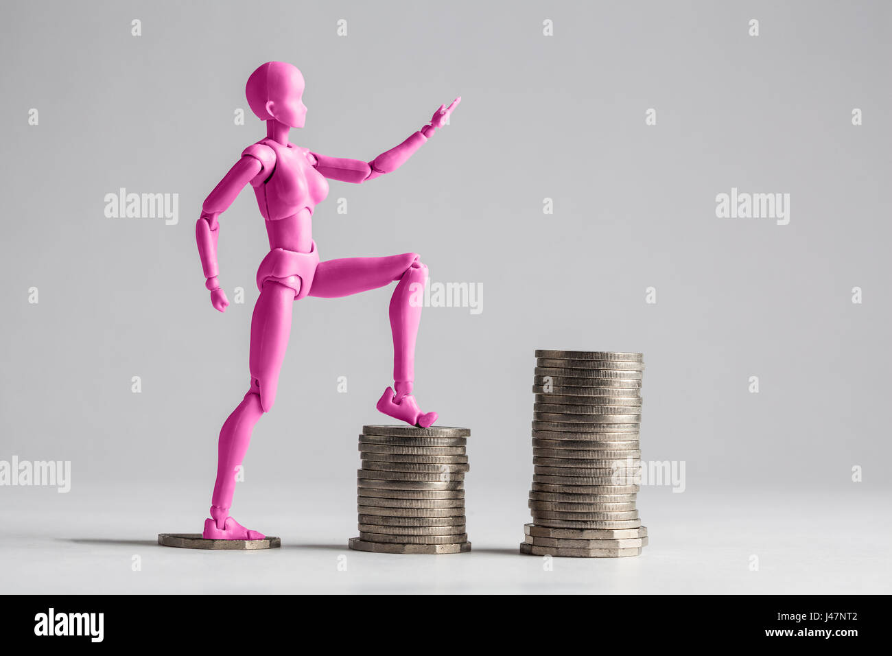 Empowered women stepping up the income ladder concept. Pink female figurine clilmbing up on piles of coins. Isolated Stock Photo