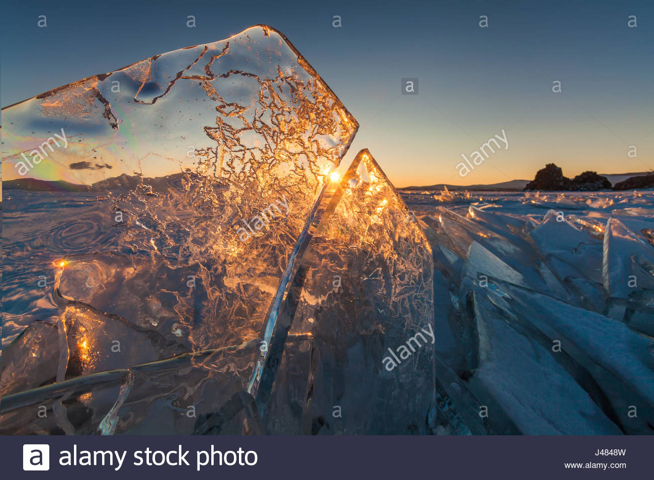 Colorful sunset over the crystal ice of Baikal lake - Stock Image