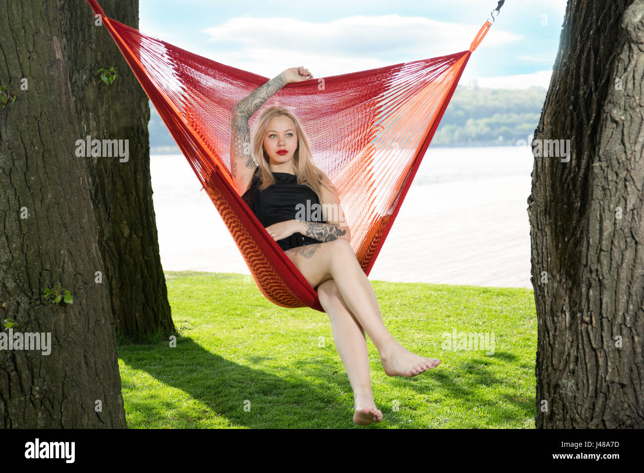 Young blonde woman resting on hammock On a background of green grass and blue sky - Stock Image