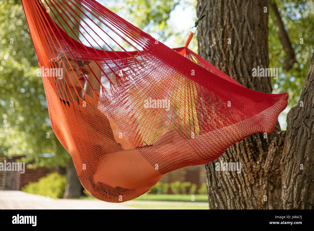 Young blonde woman resting on hammock - Stock Image