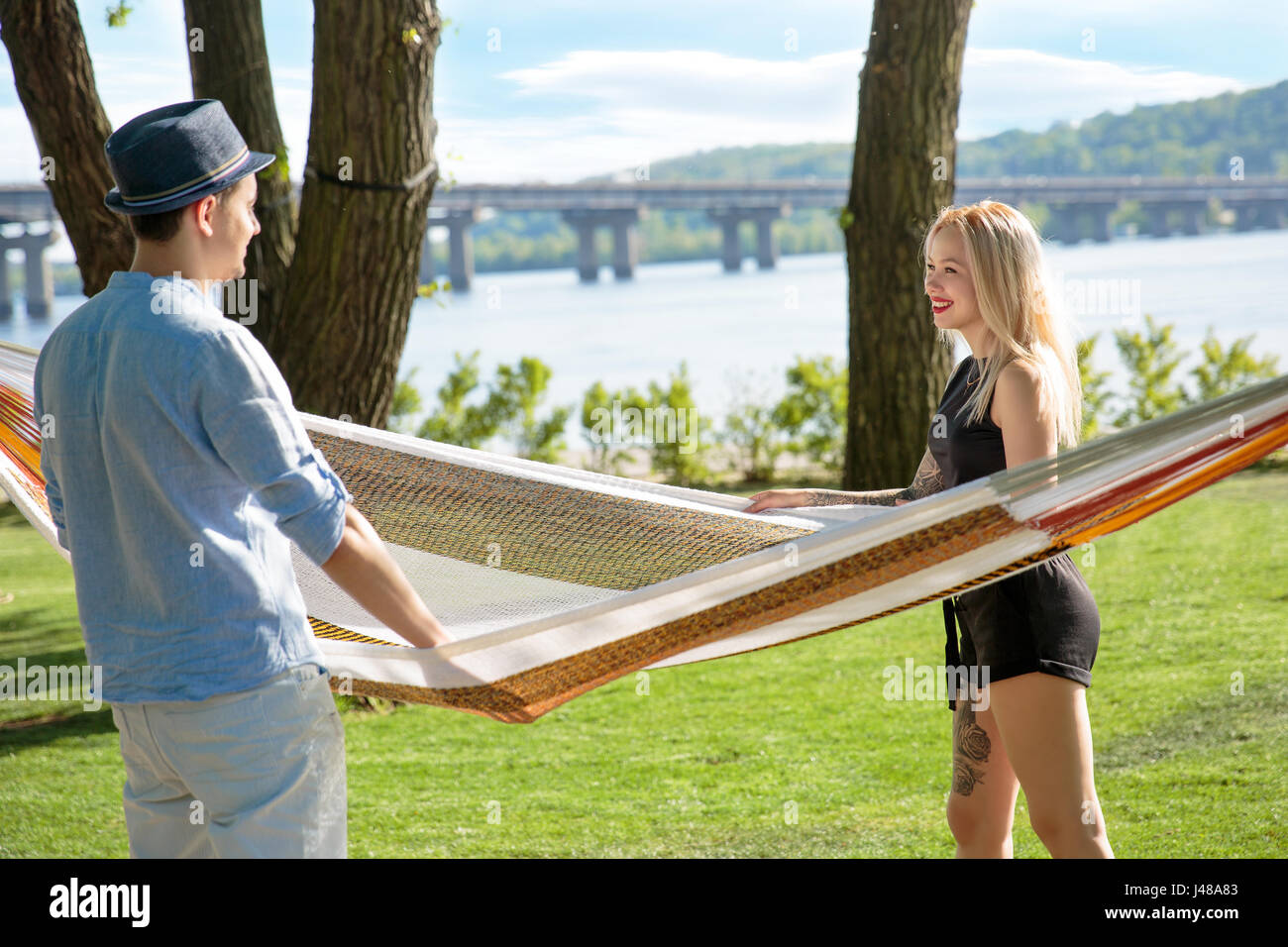 Picture of romantic couple near hammock - Stock Image