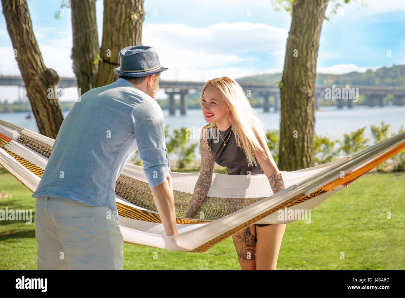 Picture of romantic couple near hammock - Stock Image
