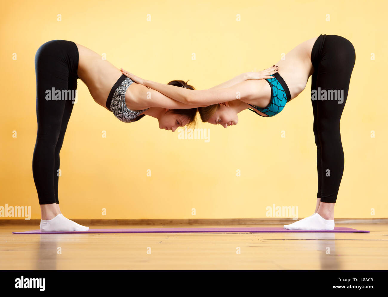 Two young women doing yoga - Stock Image