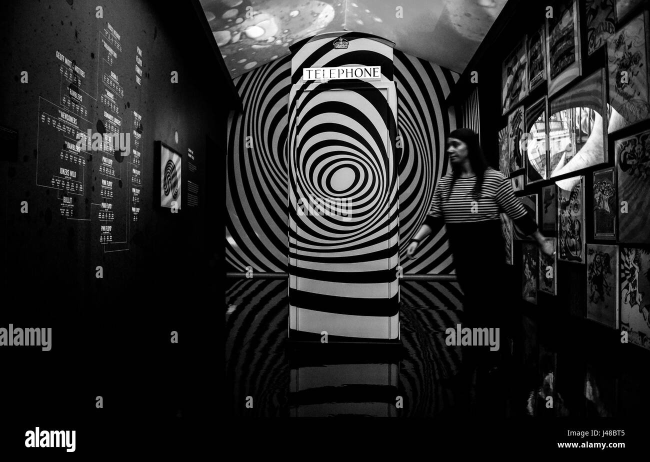 CONVERTED TO BLACK AND WHITE A member of staff walks past a telephone box in a room decorated to the theme of London's - Stock Image