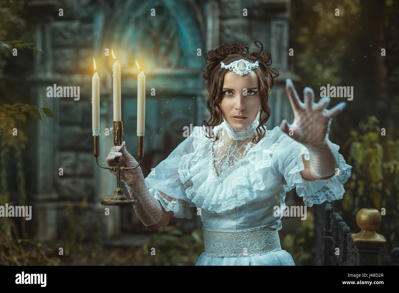 The evening darkens. Girl with a candelabra in hand in which candles are burning. Girl scares us and shouts inducing - Stock Image