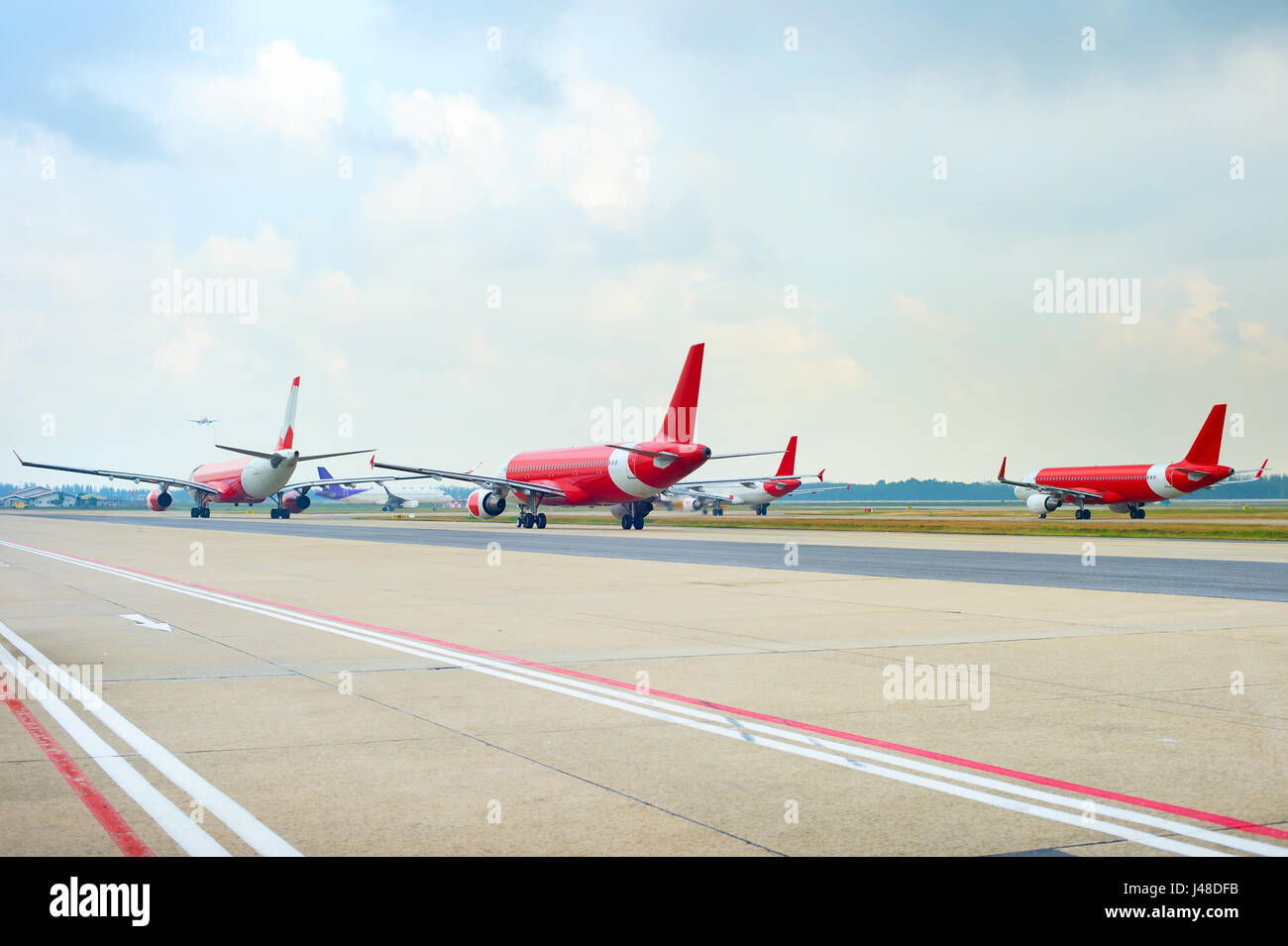 Airplanes at runway in an airport waiting for takeoff - Stock Image