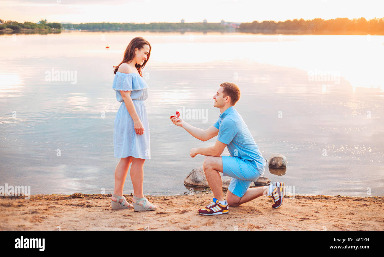 Marriage proposal on sunset . young man makes a proposal of betrothal to his girlfriend on the beach - Stock Image