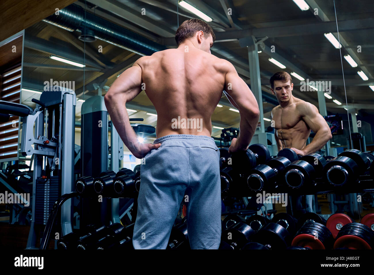 Rear view of a sporty man with muscles in the gym Stock Photo