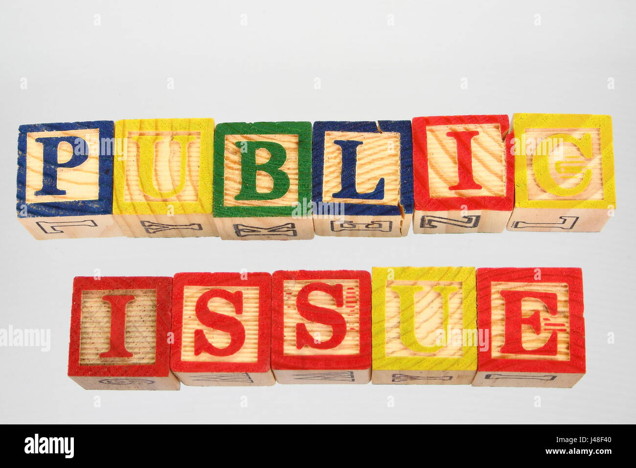 The phrase public issue displayed visually on a white background using colorful wooden blocks Stock Photo