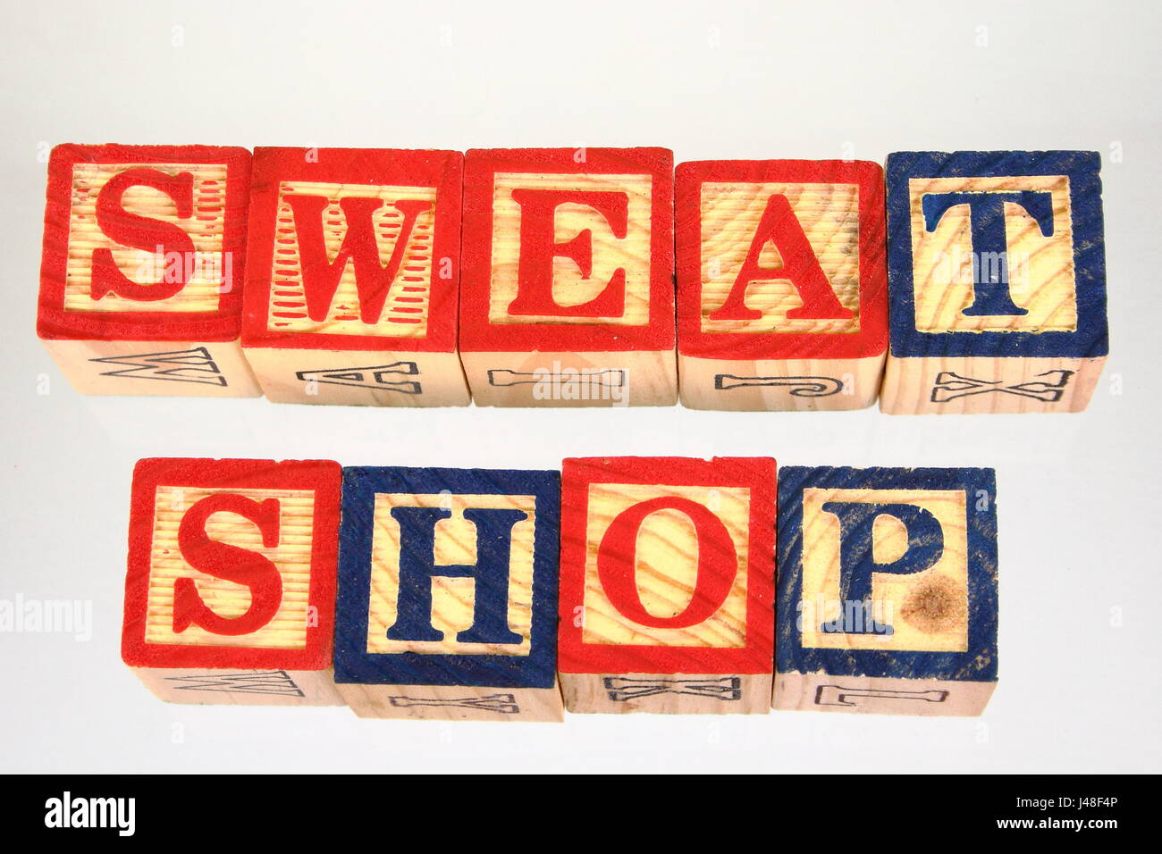 The phrase sweat shop displayed visually on a white background using colorful wooden blocks - Stock Image