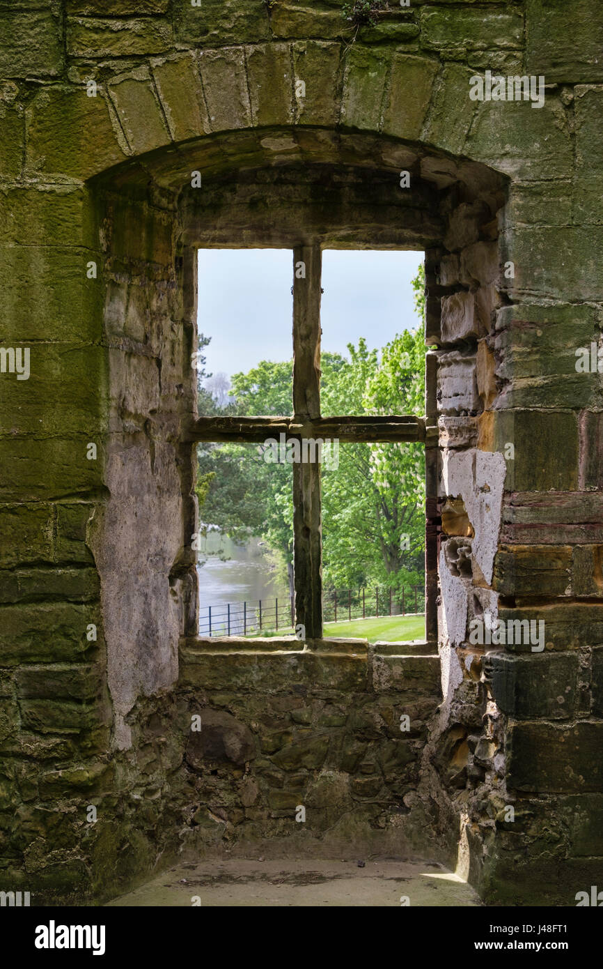 View through a stone window frame to River Ure from inside 15th-century Marmion Tower ruin. West Tanfield, North - Stock Image