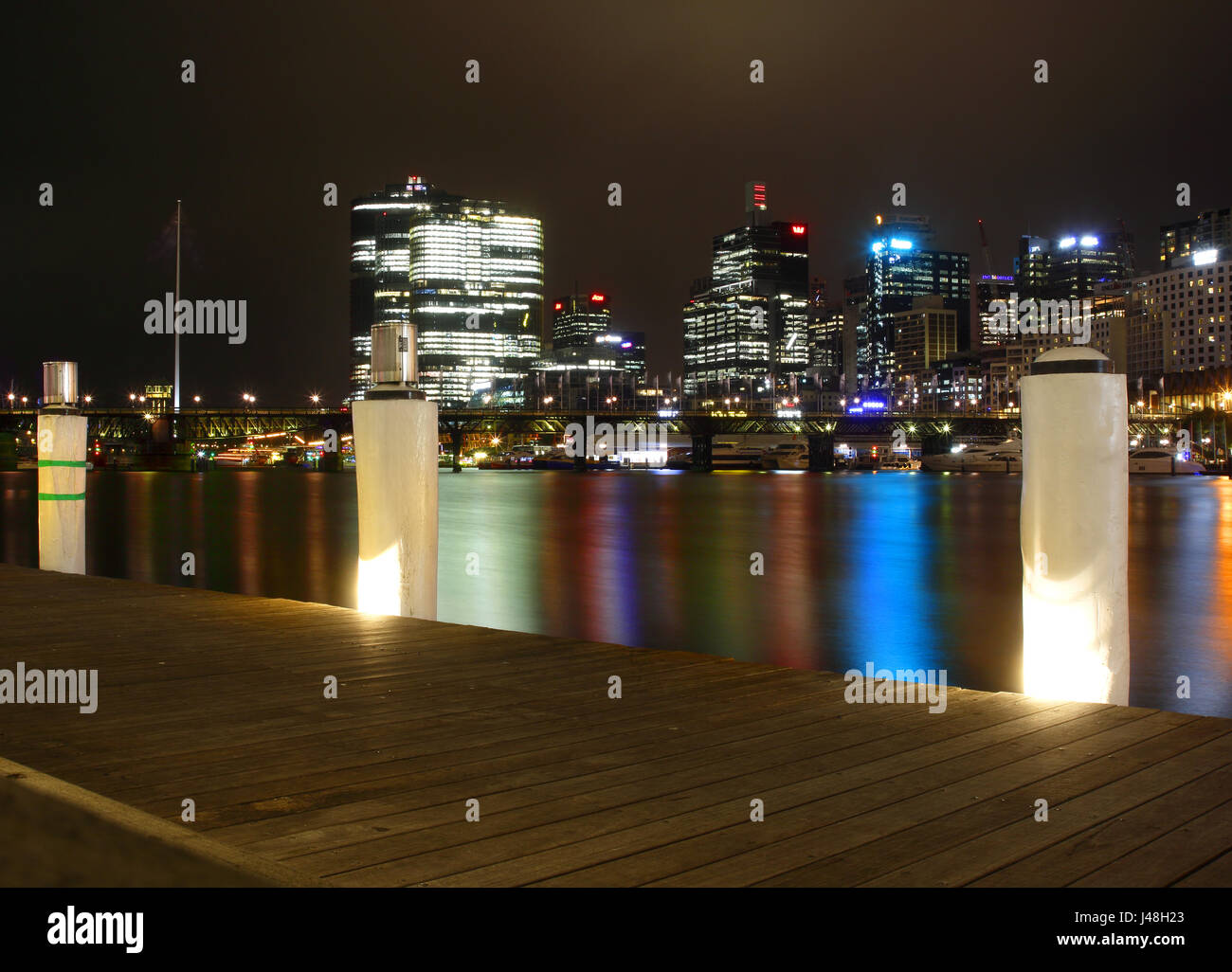 A night view accross Cockle Bay, Darling Harbour, Sydney showing reflections in the water of lights from restaurants - Stock Image