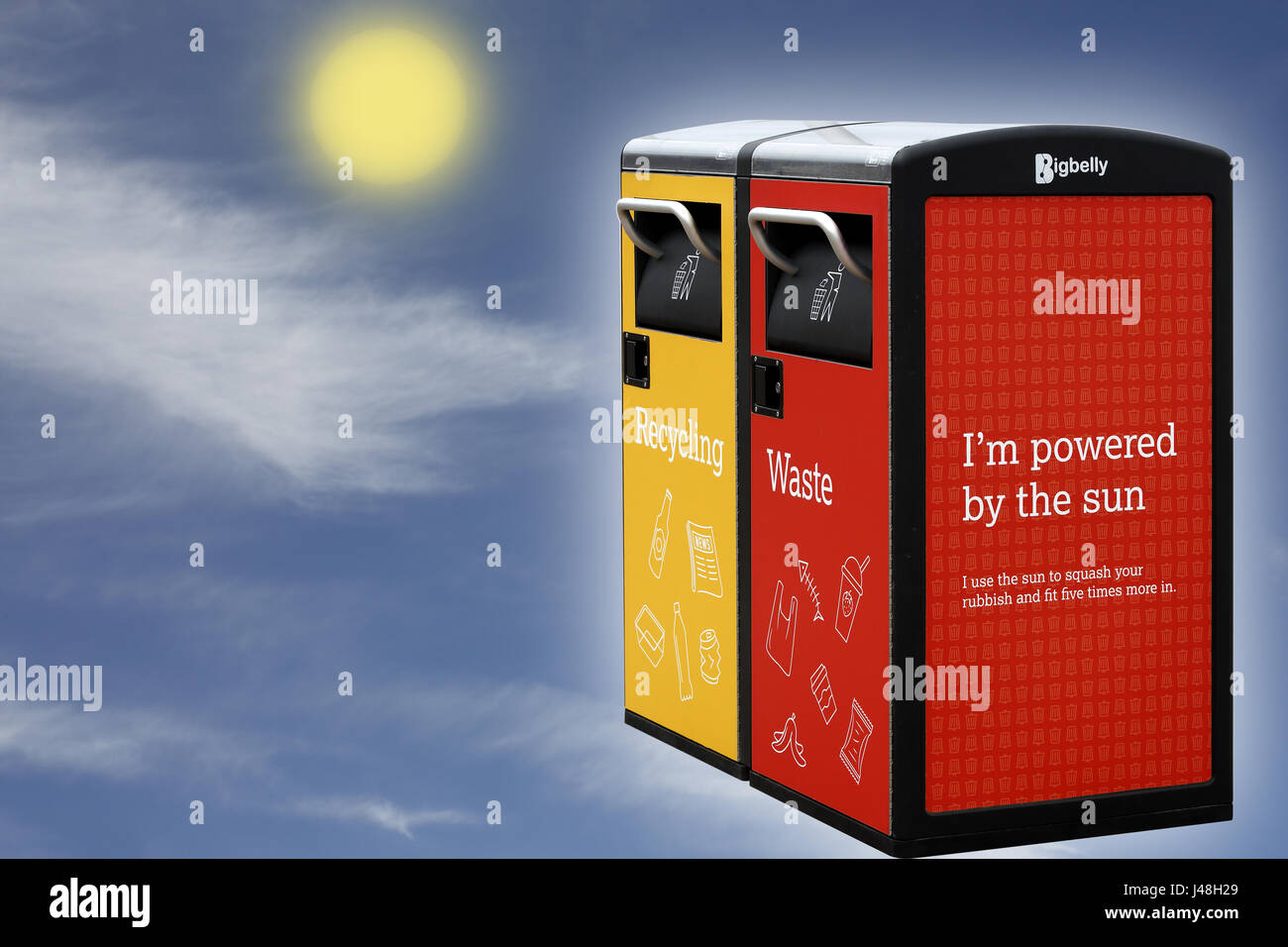 A yellow recycling bin and a red waste bin which use solar power to compact the waste. Merged image which allows - Stock Image