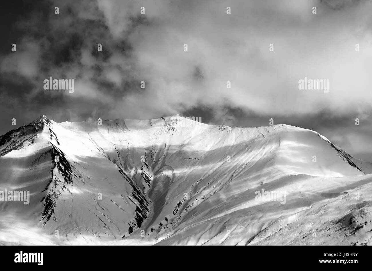 Black and white view on off-piste snow slope in evening. Caucasus Mountains, Georgia, region Gudauri. - Stock Image