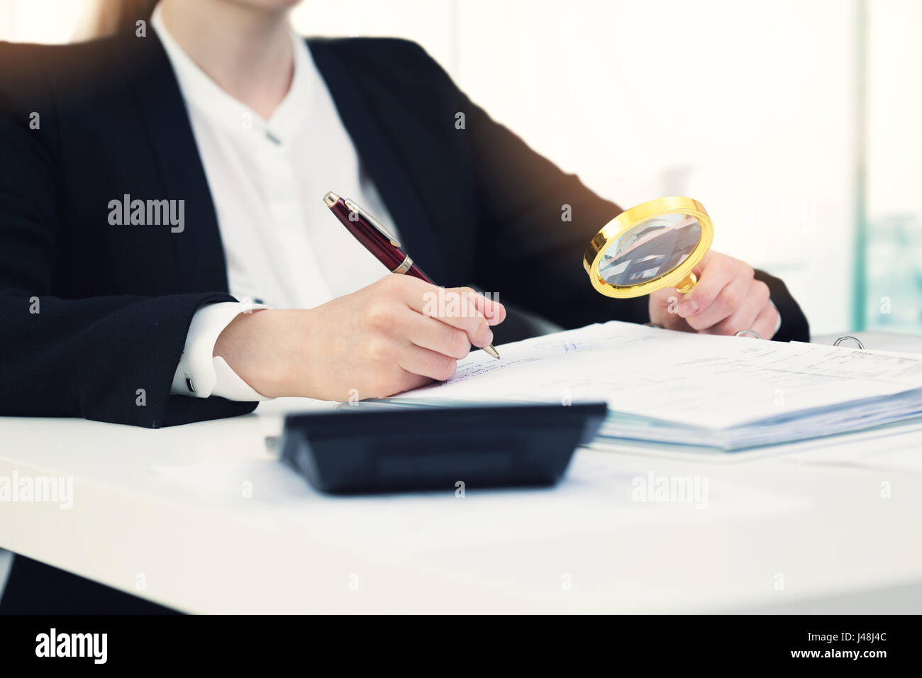 audit concept - auditor with magnifying glass inspecting documents in office - Stock Image