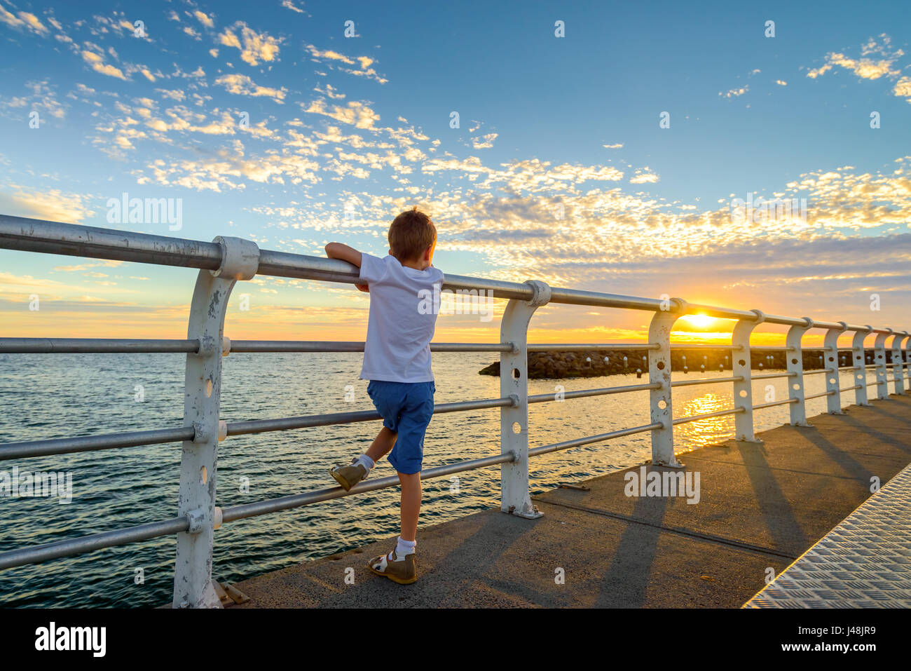Boy watching sunset from St. Kilda Jetty Melbourne, Victoria, Australia - Stock Image