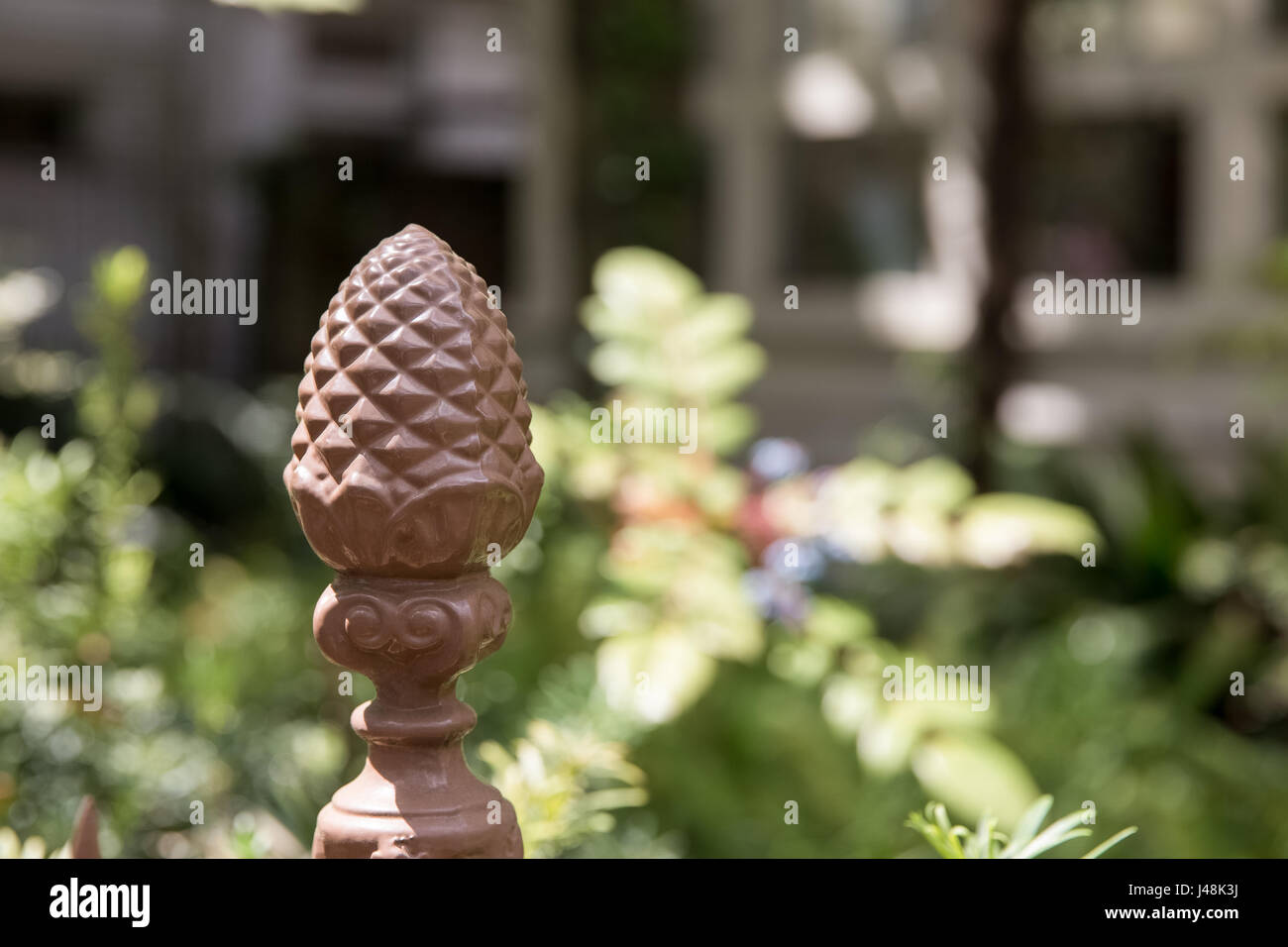 Pineapple fence post in an outdoor garden, which is symbolic of hospitality in the US.  Selective focus on the pineapple. - Stock Image