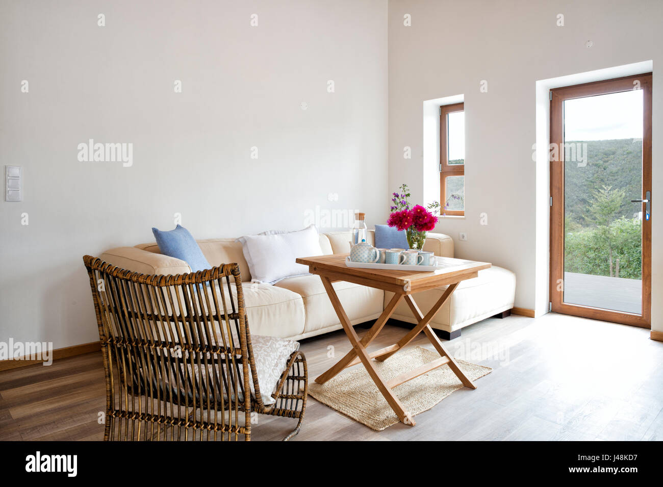 contemporary sitting room with wooden table with china tea set - Stock Image