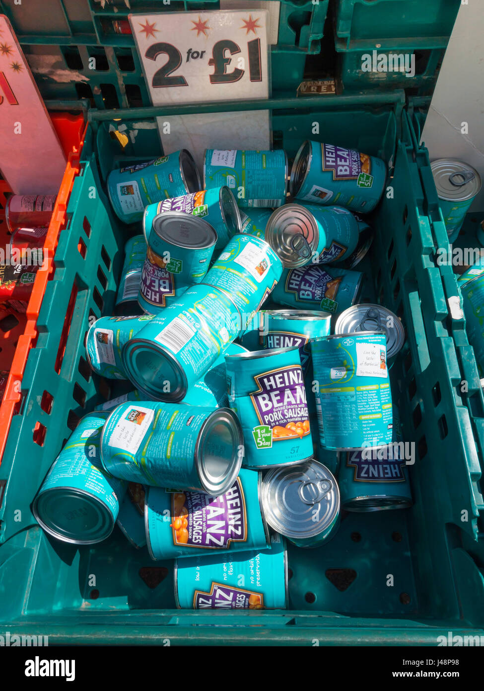 Display of damaged tins of Heinz baked beans and pork sausages for sale on a stall at a weekly market in North Yorkshire - Stock Image